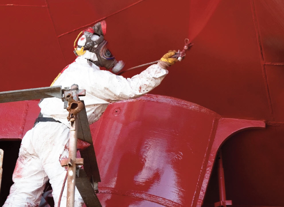 Man spraying paint on a ship
