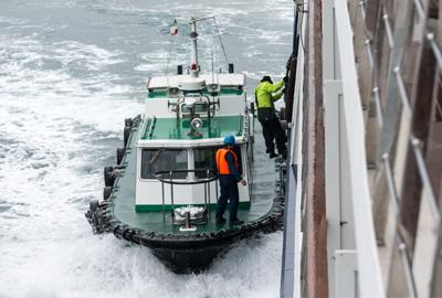 People on tug boat climbing onboard